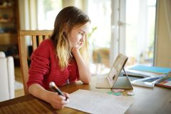 在家做她的与数字片剂的聪明的女小学生家庭作业 使用学习的小配件的孩子 教育和学会孩子的 图库摄影