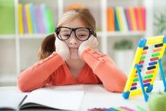 在家做她的家庭作业的不快乐的乏味红发女孩 免版税库存图片