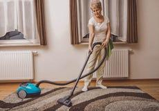 在家做妇女差事的年长妇女 Vacumming地毯 库存照片