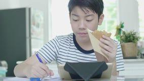 在家做家庭作业与一个愉快的表示的亚裔男孩,当在拿着食物时的手上 股票视频