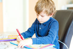在家做家庭作业与五颜六色的笔的学龄前孩子男孩文字信件 库存图片