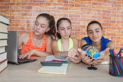 在家做家庭作业的三个少年女孩在桌上 有堆的学习女孩的学生书和笔记户内 库存图片