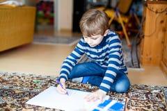 在家做家庭作业的学龄前孩子男孩,绘与五颜六色的笔的一个故事 免版税库存图片