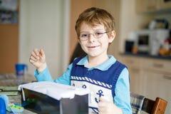 在家做家庭作业的学龄前孩子男孩,绘与五颜六色的笔的一个故事 图库摄影