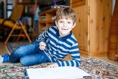 在家做家庭作业的学龄前孩子男孩,绘与五颜六色的笔的一个故事 免版税图库摄影