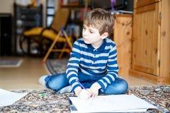 在家做家庭作业的学龄前孩子男孩,绘与五颜六色的笔的一个故事 免版税库存照片