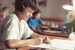 在家做家庭作业的愉快的年轻男孩 库存图片