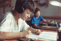 在家做家庭作业的愉快的矮小的男小学生 图库摄影
