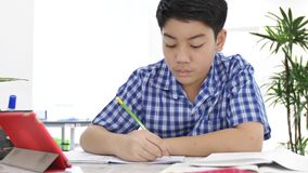 在家做您的与微笑面孔的亚裔逗人喜爱的男孩家庭作业,4K移动式摄影车射击了 影视素材