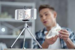 在家做新的录影的机敏的年轻博客作者 库存照片