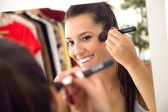 在家做构成的美丽的少妇在镜子附近 免版税库存照片