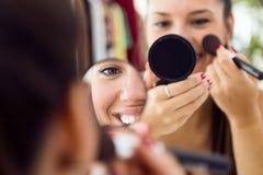 在家做构成的美丽的少妇在镜子附近 免版税库存图片