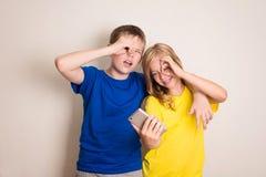 在家做照片的两最好的朋友青少年在他们的照相机,有乐趣一起,喜悦和幸福 免版税图库摄影