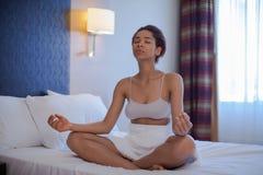 在家做瑜伽在莲花坐的年轻黑人妇女 库存照片