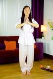 在家做瑜伽的亚裔妇女站立 免版税库存照片