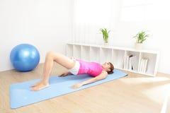 在家做瑜伽的健康少妇 免版税库存图片
