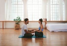 在家做瑜伽的美好的年轻夫妇 免版税库存图片
