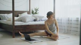 在家做瑜伽锻炼和观看在便携式计算机上的年轻可爱的妇女讲解教训 库存图片
