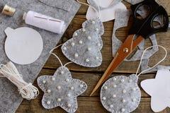在家做的容易的圣诞节工艺 灰色感觉用白色小珠和星装饰的杉树、球,剪刀,螺纹,针 免版税图库摄影