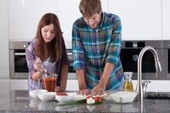 在家做薄饼的夫妇 免版税库存照片