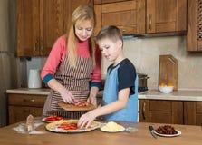 在家做薄饼的妇女和她的儿子 烹调与他的母亲的少年男孩 图库摄影