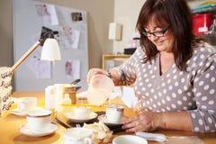 在家做蜡烛的成熟妇女 免版税库存图片