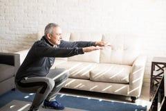 在家做蹲坐锻炼的成熟人 图库摄影
