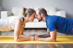 在家做锻炼的年轻夫妇在客厅 免版税库存照片