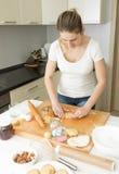 在家做面团的美丽的少妇在厨房 免版税库存照片
