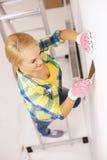 在家做整修的手套的微笑的妇女 免版税库存照片