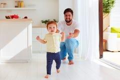 在家做他的第一步的逗人喜爱的矮小的男婴 免版税库存照片