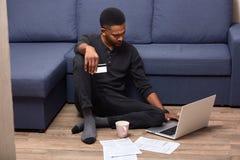 在家停留严肃的沉思美国黑人的人的图象,与联机服务被混淆,拿着信用卡,看 库存图片