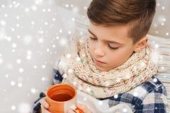 在家关闭不适的男孩用流感饮用的茶 图库摄影