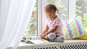 在家关闭小的逗人喜爱的女孩阅读书画象在窗台的 股票视频