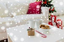 在家关闭礼物、甜点和杯子在桌上 免版税库存图片