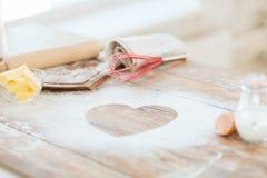 在家关闭面粉的心脏在木桌上的 库存照片