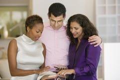 在家具店正面图的女推销员和夫妇审查的织品样片 库存照片