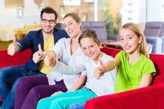 在家具店的家庭买的长沙发 免版税库存照片