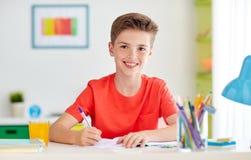 在家写给笔记本的愉快的学生男孩 免版税库存照片