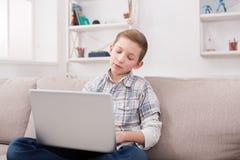 在家冲浪在膝上型计算机上的十几岁的男孩万维网在长沙发 免版税库存照片