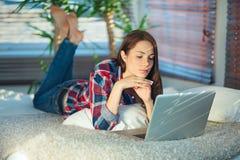 在家冲浪网的妇女 免版税图库摄影