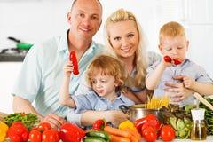 在家准备一顿健康晚餐的愉快的家庭。 免版税图库摄影