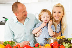 在家准备一顿健康晚餐的愉快的家庭。 免版税库存照片