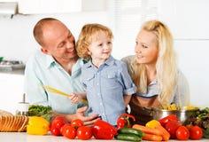 在家准备一顿健康晚餐的愉快的家庭。 免版税库存图片