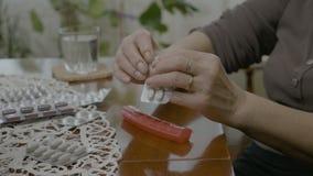 在家准备她的在一个药片组织者箱子的一个结婚的老妇人的手每日疗程药量在桌上- 影视素材
