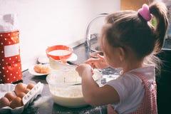在家准备面团的一个小逗人喜爱的女孩在厨房里 图库摄影