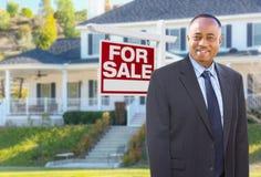 在家前面的非裔美国人的代理待售标志 库存图片