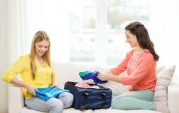 在家包装手提箱的两个微笑的十几岁的女孩 免版税库存图片