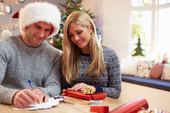在家包裹圣诞节礼物的夫妇 库存照片