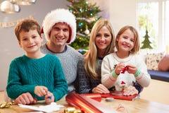 在家包裹圣诞节礼物的家庭 免版税图库摄影